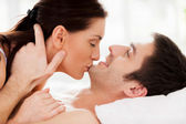 Loving couple lying in bed while woman kissing her boyfriend chin — Stock Photo