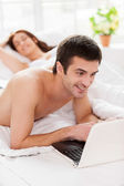 Man using laptop while lying in bed with his girlfriend — Stock Photo