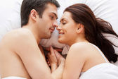 Loving couple lying in bed and holding hands — Stock Photo