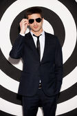 Young man in full suit adjusting his sunglasses — Stock Photo