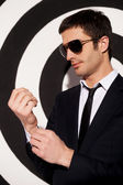Man in formalwear and sunglasses adjusting his shirt cuffs — Stock Photo