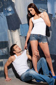 Beautiful young couple in tank tops and jeans — Stock Photo