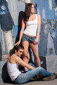 Couple in tank tops and jeans posing against jeans background — Foto Stock