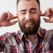 Bearded man making a face and covering ears by fingers — Stock Photo #42046797