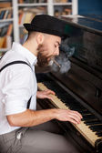 Profile of bearded men playing piano and smoking cigarette — Stock Photo