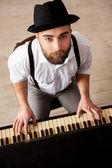 Top view of bearded men playing piano and looking at camera — Stock Photo