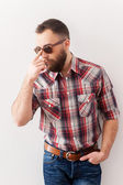 Man in casual wear adjusting his sunglasses and holding one hand in pockets — Stock Photo