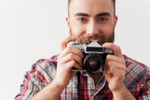 Young beard man focusing at you with his retro camera — Stock Photo