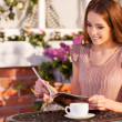 Woman reading magazine while sitting at the outdoor cafe — Stock Photo #42149495