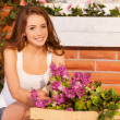 Woman arranging flowers in the pot and smiling at camera — Stock Photo