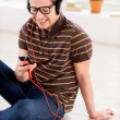 Man looking at his mp3 player and listening to the music — Stock Photo