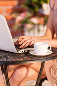 Woman working at laptop while sitting at the outdoor cafe — Stock Photo