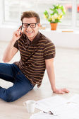 Man in glasses working on laptop while sitting on the floor — Stock Photo