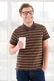 Handsome young man holding a cup and smiling — Stockfoto