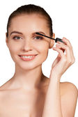 Woman holding make-up brush on eyebrow and smiling — Stock Photo