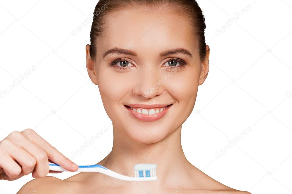 depositphotos_42352437-Woman-holding-toothbrush-with-toothpaste-and-smiling-at-camera.jpg