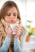 Young woman in scurf drinking hot tea — Stock Photo