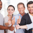 Group of cheerful business people in casual showing their thumbs up — Stock Photo #42491485
