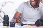 African man sitting at his working place and writing something — Stock Photo