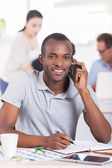 African man talking on the mobile phone and smiling — Stock Photo