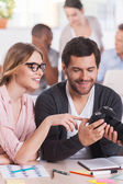 Co-workers holding camera and smiling — Stock Photo