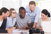 Group of cheerful business people sitting together — Stock Photo