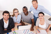 Group of business people in casual wear sitting together at the table — Stock Photo