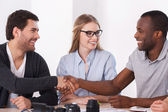 Two business people handshaking while woman sitting between them — Stock Photo