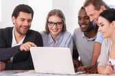 Group of business people discussing something while looking at the laptop — Stock Photo