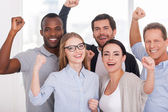 Business people in standing and keeping arms raised — Stock Photo