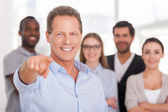 Man pointing you and smiling while group of people standing on background — Stock Photo