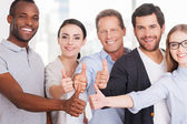 Group of cheerful business people in casual showing their thumbs up — Stock Photo