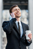 Man talking on the mobile phone and holding coffee — Foto de Stock