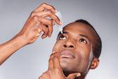 African man applying eye drops — Stock Photo