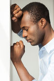 African man in blue shirt leaning at the wall — Stock Photo