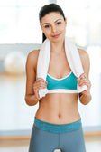 Woman in sports clothing holding towel — Stock Photo