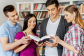 Four cheerful students reading a book — Stock Photo