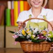 Woman stretching out basket full of flowers — Stock Photo #45020331