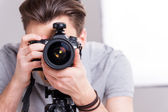 Man focusing at you with digital camera — Stock Photo
