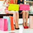 Women shopping. Cropped image of two young women sitting in shopping mall with bags — Stock Photo