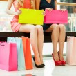 Women shopping. Cropped image of two young women sitting in shopping mall with bags — Stock Photo #45052577
