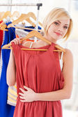 Woman choosing dress to wear — Stock Photo