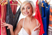 Woman looking out from the dresses in closet — Stock Photo