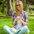 Student sitting in a park with books — Stock Photo