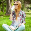 Student drinking coffee in a park with books — Stock Photo #45852855