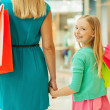 Mother and daughter holding shopping bags — Stock Photo