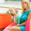 Mother and daughter on bench in shopping mall — Stock Photo #45918847