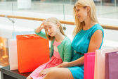 Mother and daughter on bench in shopping mall — Stock Photo