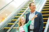 Father and daughter moving down by escalator — Stock Photo