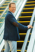 Mature man moving up by escalator — Stock Photo